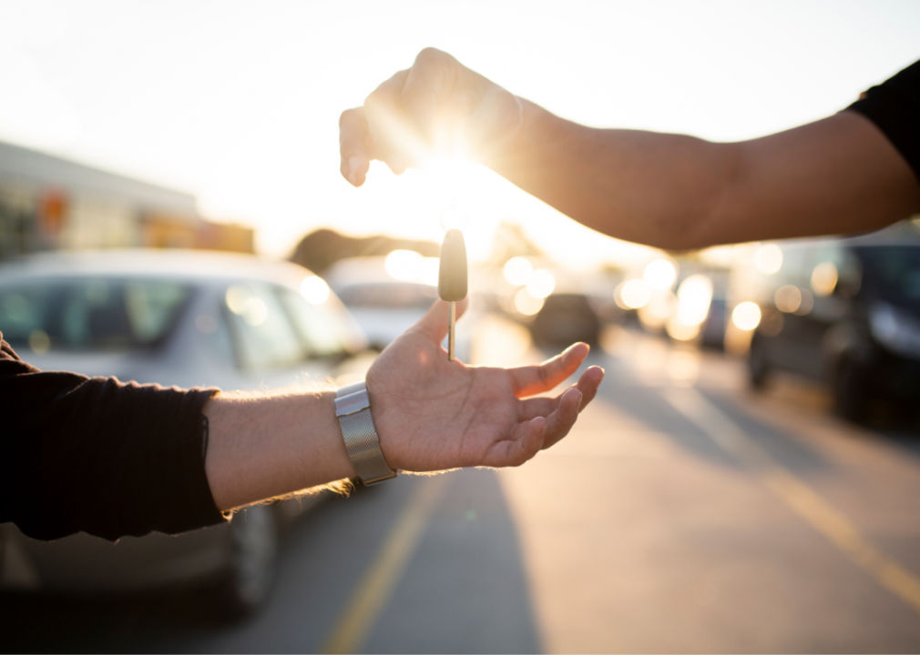Photo of car keys being handed from one person to another