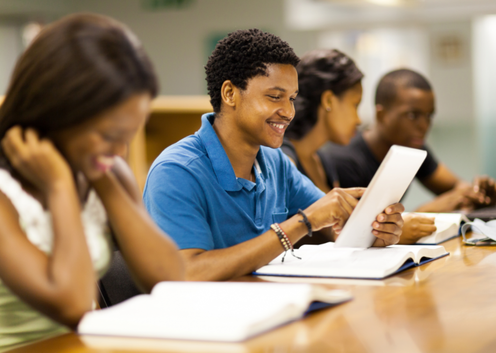Students with textbooks at a shared desk space