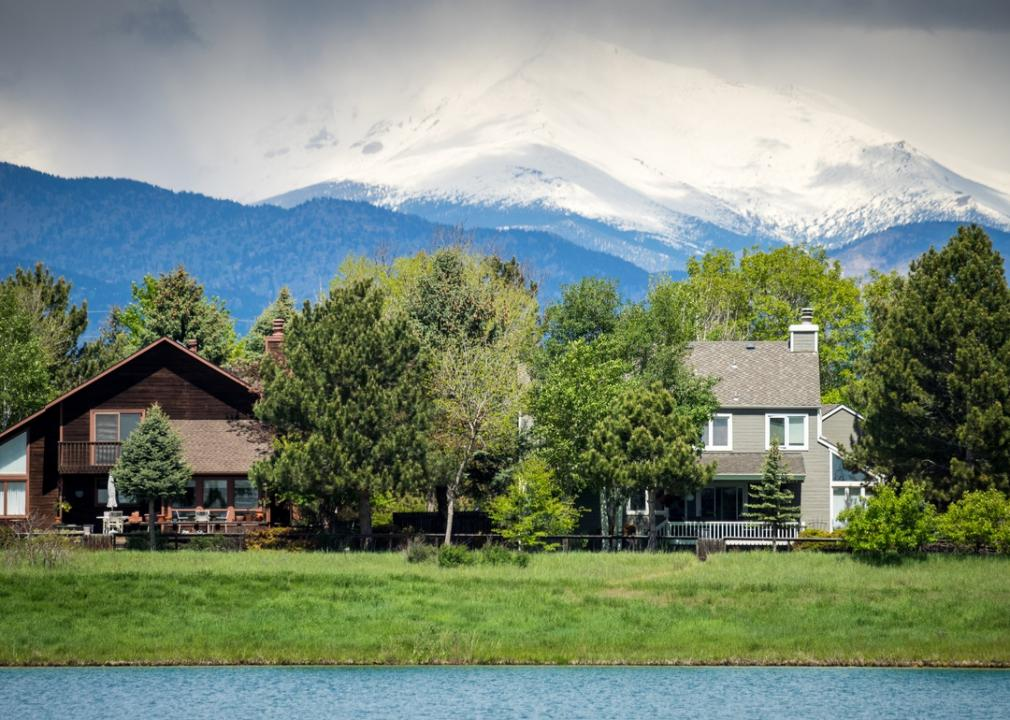 Colorado, two homes on a river with a mountain in the background