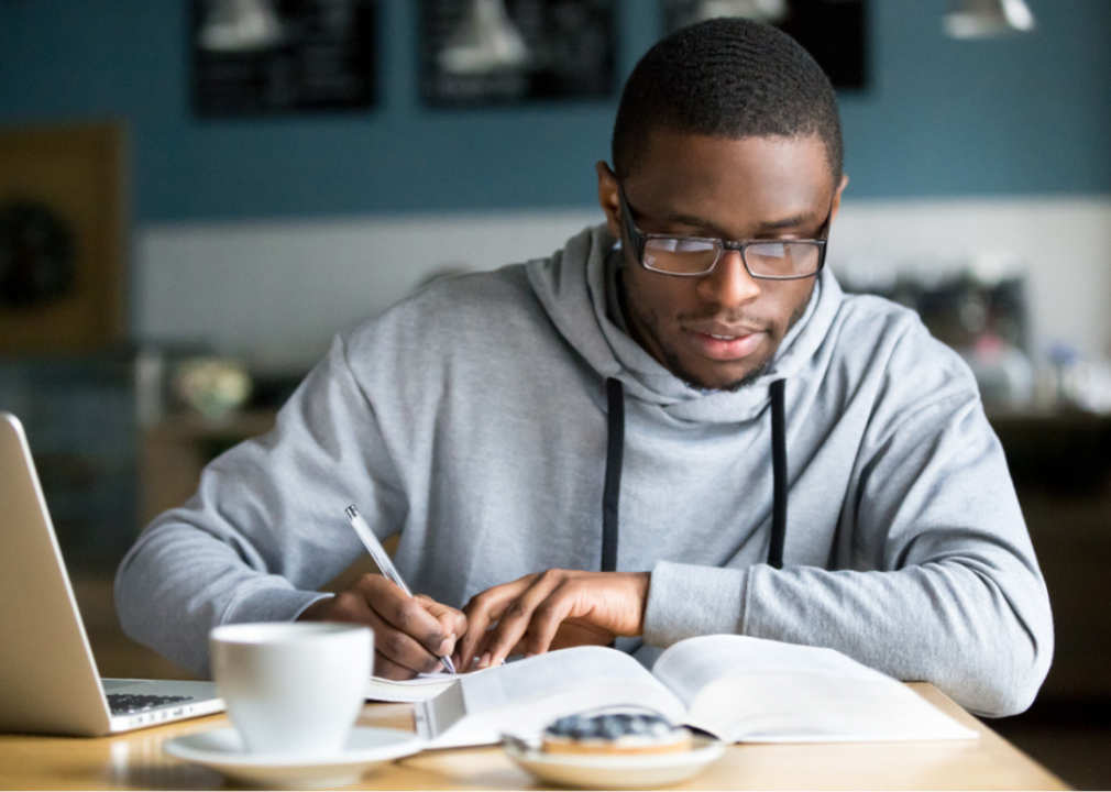 An African American student in glasses making notes from a text book in a cafe