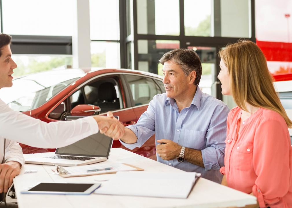 Photo of a couple purchasing a used car at a dealership