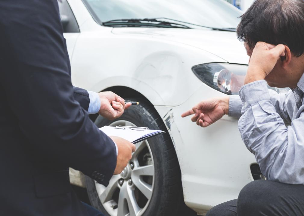 Photo of people inspecting a damaged area on a used car