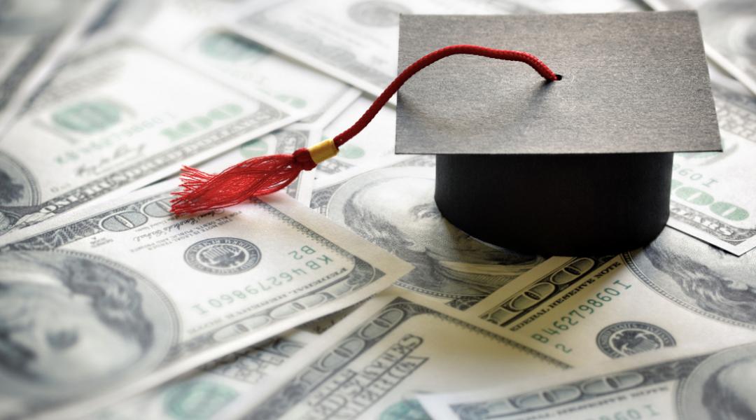 a graduation cap resting on money